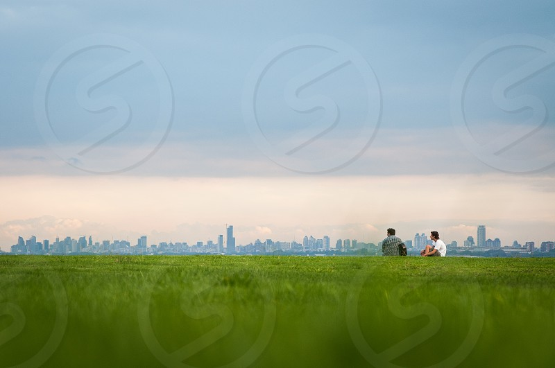 outdoor shot over green grass in the distance diverse groups of little people connected and inspired by nature photo