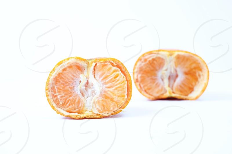 Fresh half cut orange one sliced orange behind it isolated in white background photo