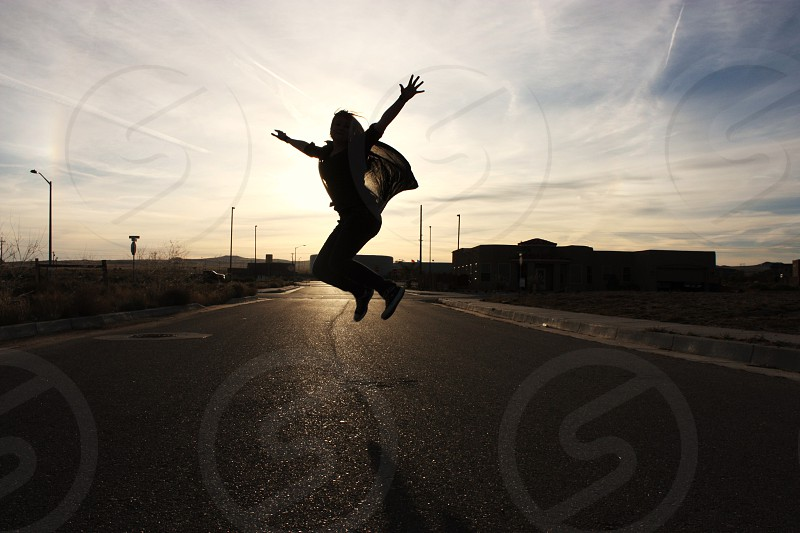 person taking a jump shot on black concrete road photo