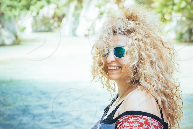 Happy Blonde Woman With Mirrored Sunglasses On Vacation During Daytime photo