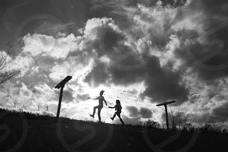 two people walking under cloudy sky during daytime photo