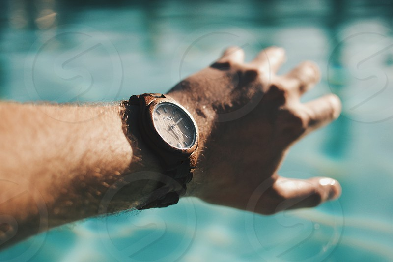 person wearing brown link analog watch photo