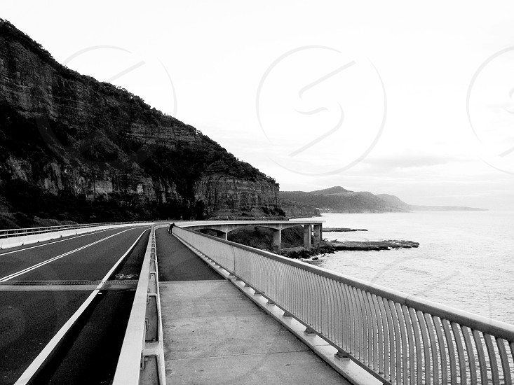 concrete roadway beside sea view photography photo