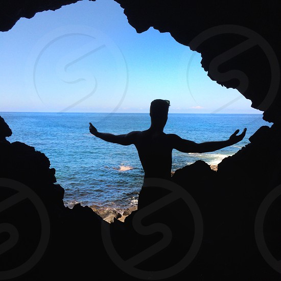 silhouette of person inside the cave photo