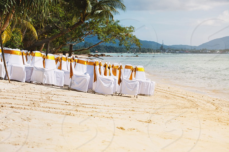Beach wedding venue preparation using white cover chairs organza with gold sash decoration on the sunny day Samui island Thailand photo
