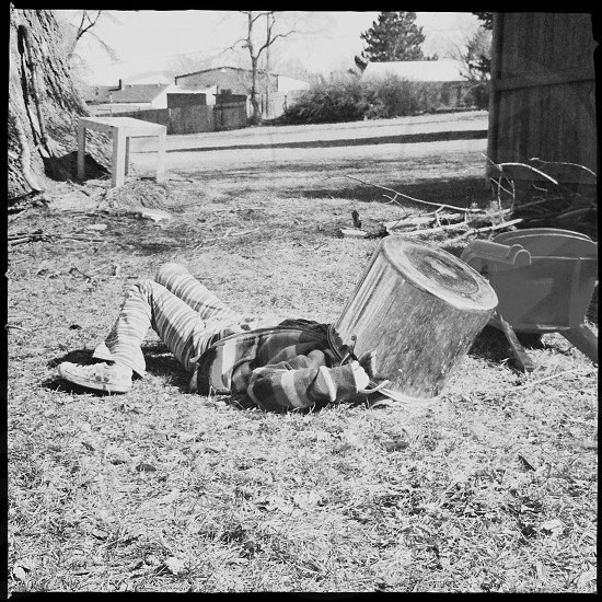 man lying on ground with cooking on the head in grayscale photography photo