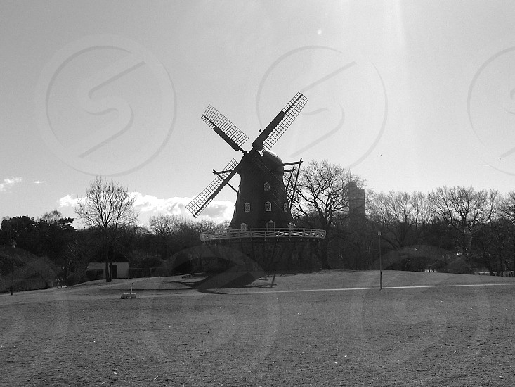 grey wooden windmill near the trees photo