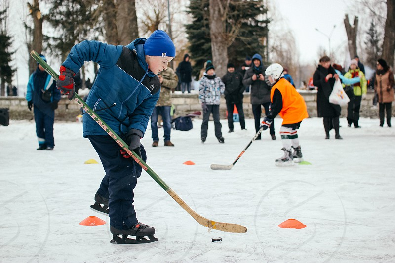 Young guy practising his hockey skills with other guys photo
