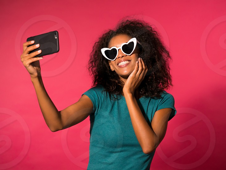 Beautiful african american woman with afro hair in yellow wear and sunglasses smiling to camera over white wall background. Cute mixed race girl's portrait with amazement photo