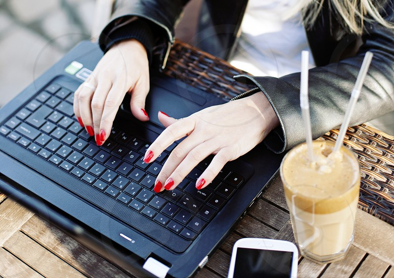 Female typing on lap top in cafe drinking coffee with mobile phone photo