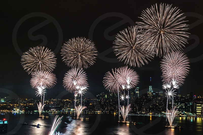 brown and purple fireworks set in boat in front of city buildings during night time photo