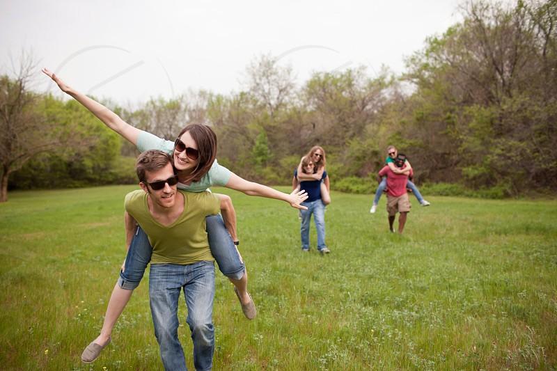 men carrying women on their backs on green grass photo