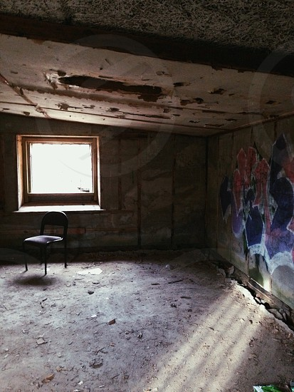 An abandoned building in Norway with a lone chair and light rays and shadows. photo