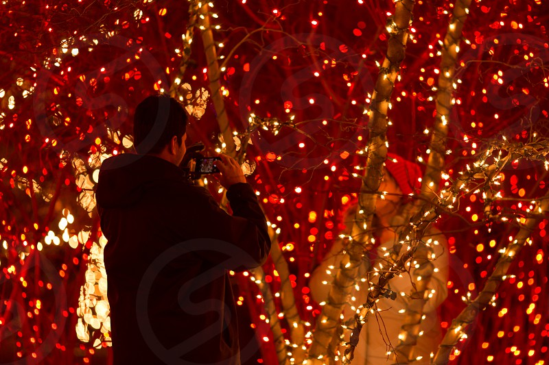 A man taking a photo of a woman surrounded by Christmas lights photo