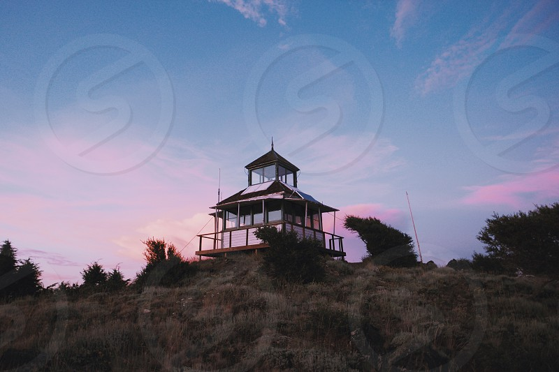 white wood house on cliff under blue pink sky photo