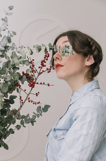 woman wearing white collared shirt standing near red berries and green leaves photo