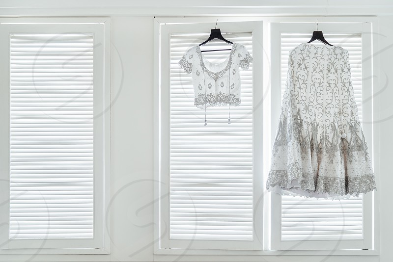 Luxury Indian wedding dress saree (shari) and blouse of indian bride hanging on the white wall windows with soft light with copy space photo