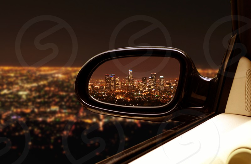 black car left wing mirror with the city view reflection photo