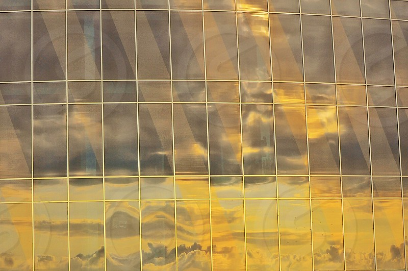 building with mirror panel with reflection of clouds photo