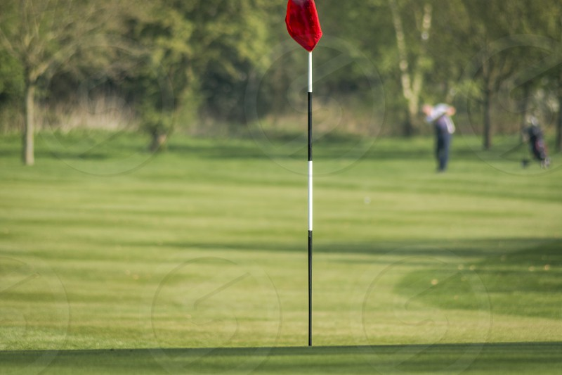 A golfer out of focus in the background playing his shot towards the flag in focus in the forground. Landscape orientation  photo