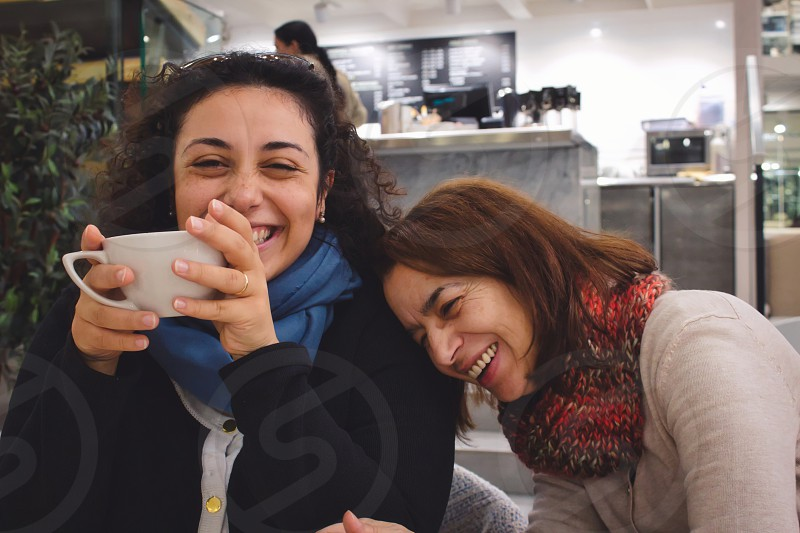 Mother and daughter enjoying a joke and a chat and a cup of coffee or tea laughing and smiling in a cafe photo