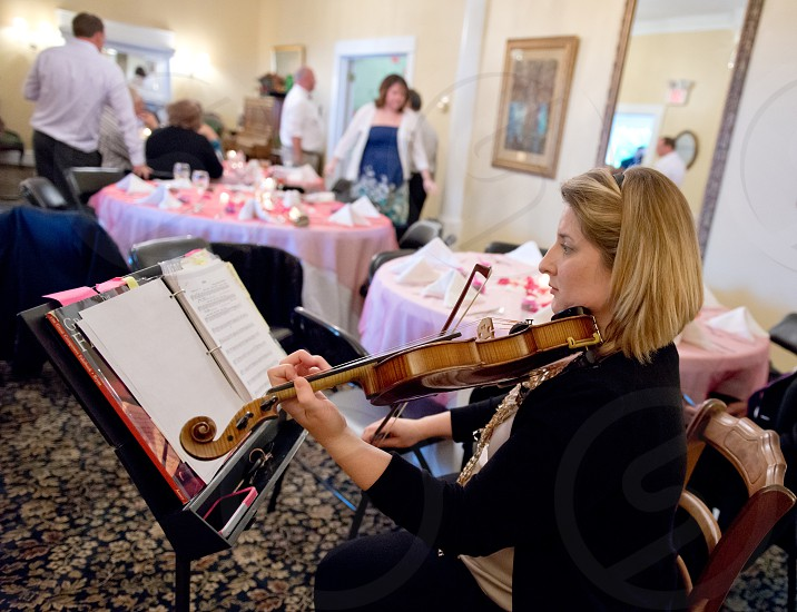 Musician playing the violin at a wedding reception.  photo