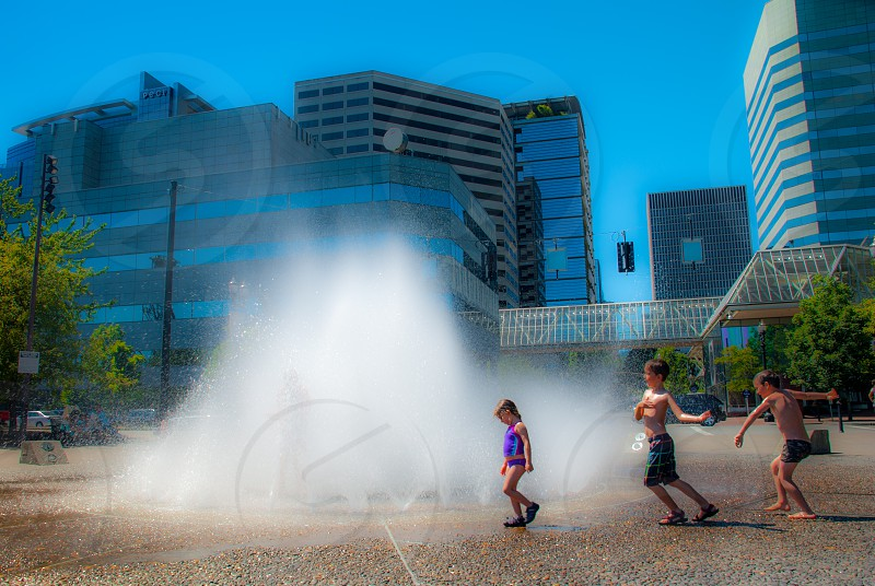 Kids playing in a waterfront fountain in downtown Portland Oregon. photo