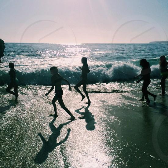 people running on grey seashore photo