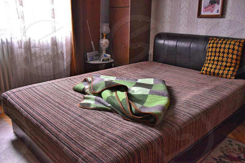 green and gray checked throw blanket on brown bedspread photo
