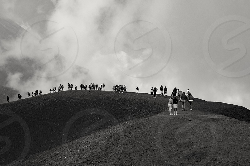 Black and white image of people walking on the rim of a crater on Mount Etna with cloud in the background... photo