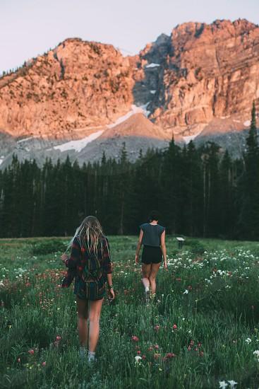 2 women walking on green field near brown mountain photo