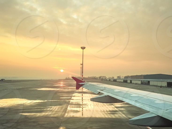 Airport And Airplane Wing At Sunrise photo