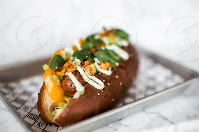 A sausage hot dog loaded with toppings including cilantro sour cream corn nuts and tomato on a seeded roll. photo