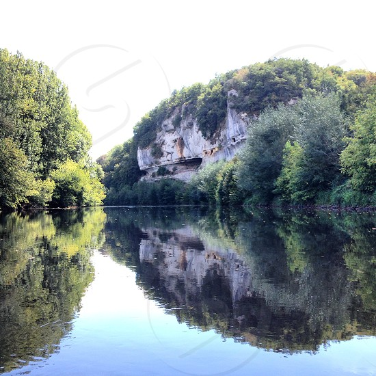 reflection of cliffside on a still river in france photo