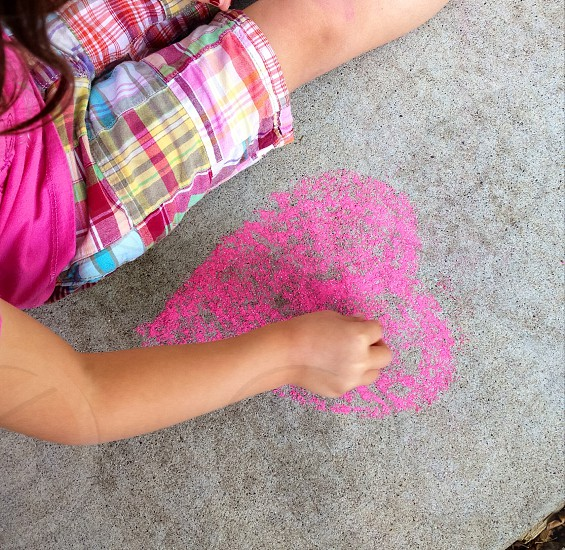 Young girl drawing pink heart on sidewalk with chalk photo