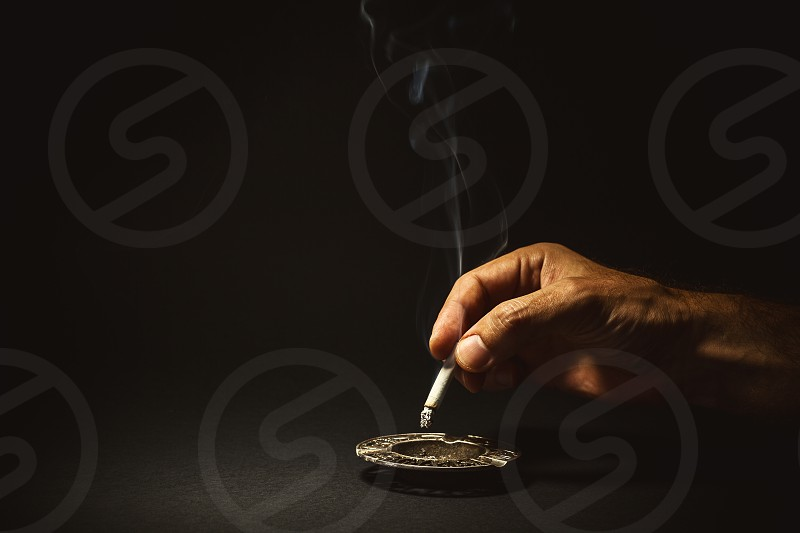Conceptual composition about quit smoking man's hand extinguishes a cigar. photo