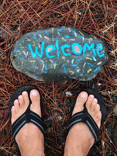 person wearing black and grey flip flops near grey stone with welcome print photo