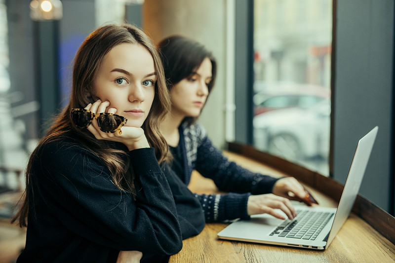 Two girls friends Drink Hot Coffee While Work In Cafe On Laptop. Portrait Of Stylish Smiling Girls In Winter Clothes Drinking Hot Coffee And Work At Laptop. Female Winter Style. - Image photo