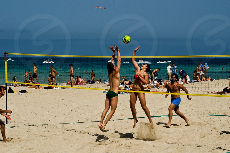 3 woman playing volleyball photo