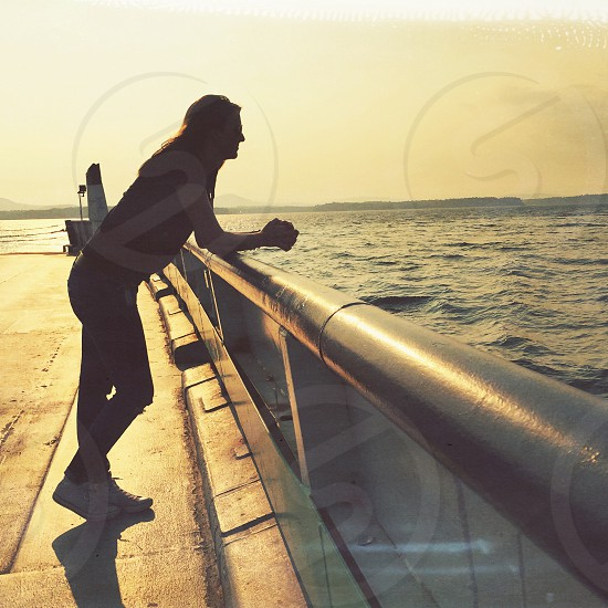 woman leaning on gray metal pipe railing near body of water wearing black t shirt black skinny jeans white shoes during twilight photo