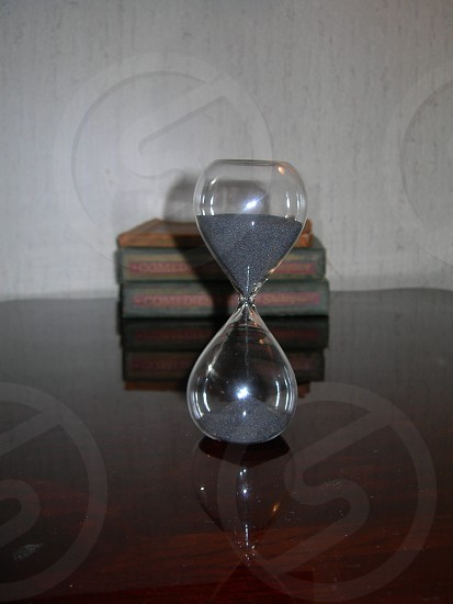 Hourglass with books in background. photo