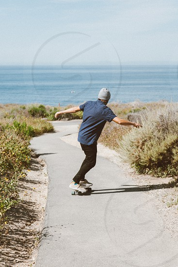 man in blue skating on concrete pathway near bushes during daytime photo
