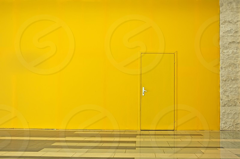 Yellow wall with a door. Horisontal background photo