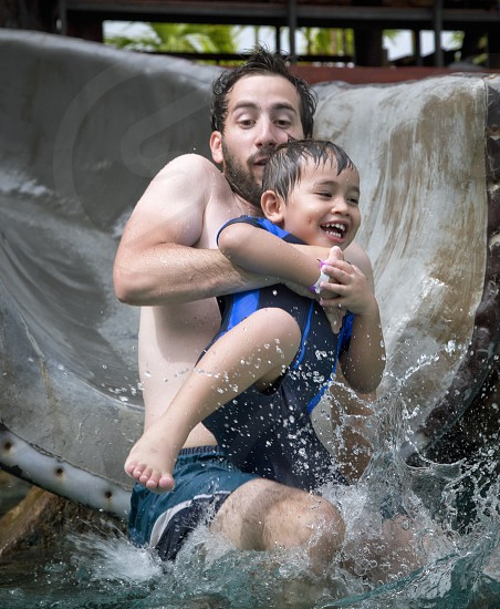 father and son having fun at the pool slide on summertime photo