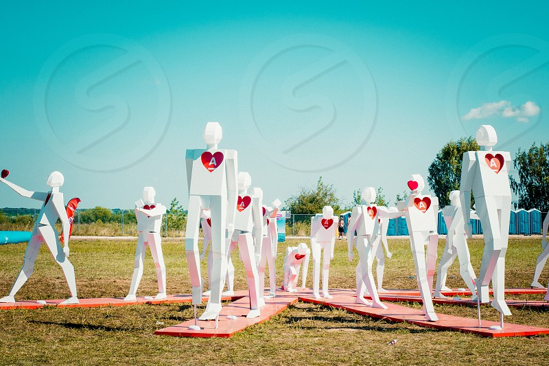 Art installation at summer music festival of white human figures with red heart signs photo