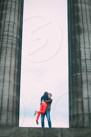 couples in the middle of tall pillars photo