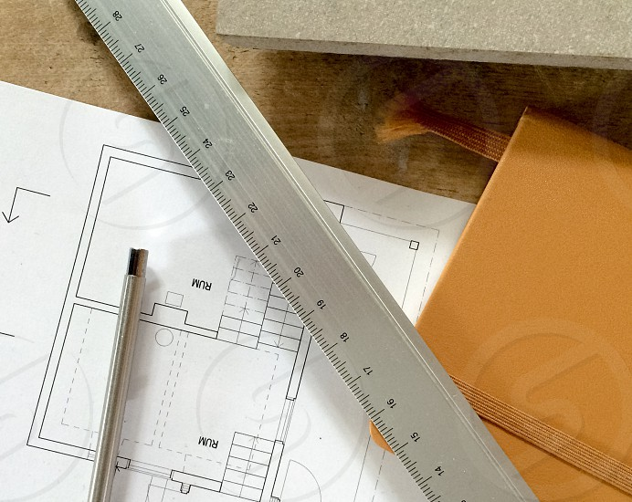 Desk with planer pen ruler and sketches on a house. photo