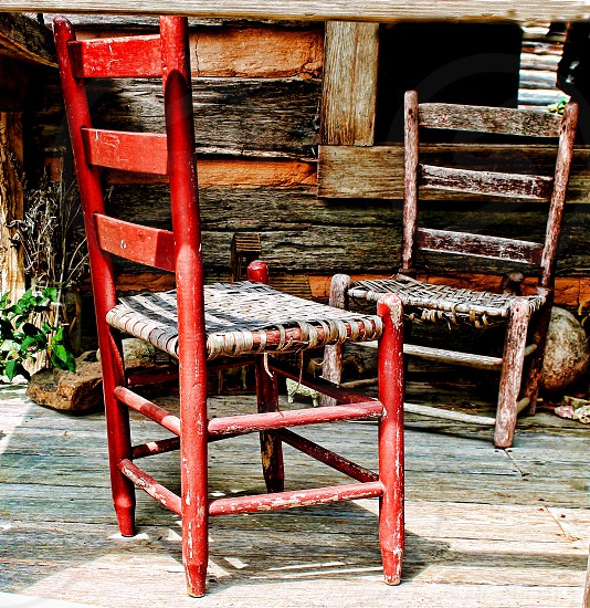 Two handmade rustic wooden chairs with straw seats are outside a log cabin. photo