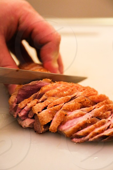 Hand cutting a piece of meat photo