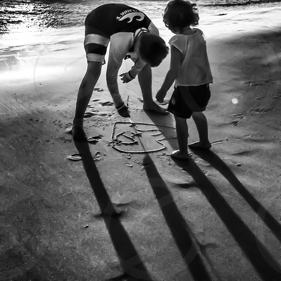 Making marks in the sand - children - playing - sand - beach - shadows -shadows playing  photo